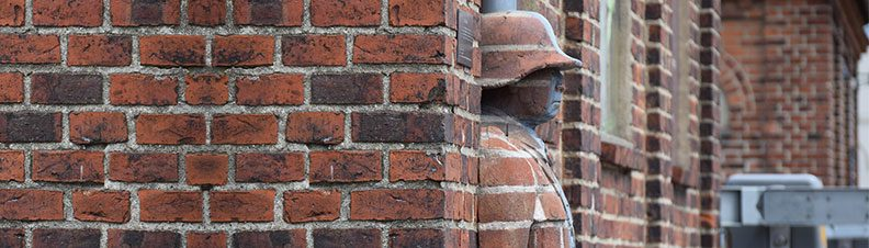 A statue of a man emerges from a brick wall
